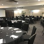 Royal coach hotel banquet function room set with round black tables and black chairs