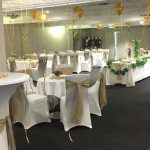 Royal coach hotel private function room set for a wedding with white chair covers and gold sashes